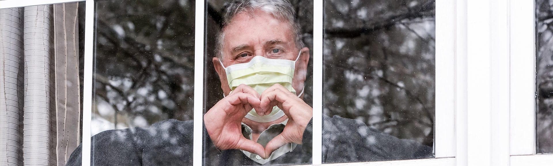 Rentner mit Maske steht in Corona Zeiten im Fenster und zeigt ein Herz