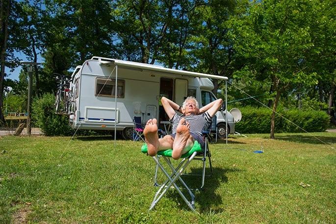 Senior im Campingstuhl genießt die Sonne vor seinem Teilkauffinanzierten Wohnmobil