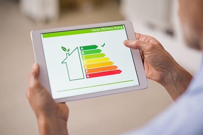 Senior betrachtet die Energieeffizienz seines Hauses auf seinem Tablet