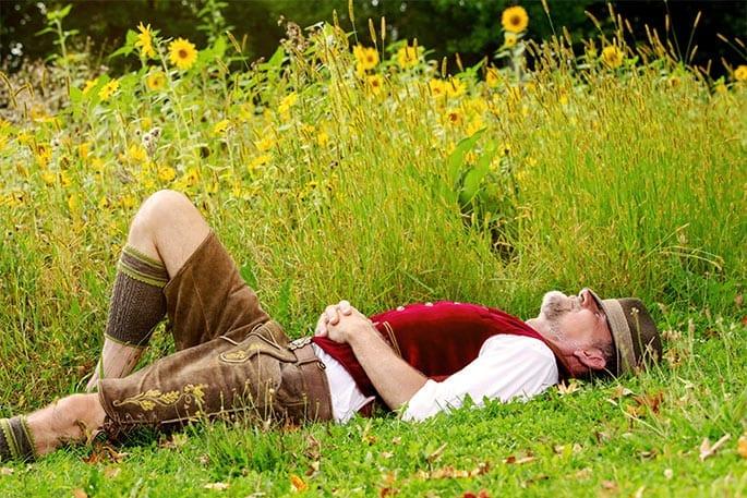 Entspannter Senior im Gras genießt die finanzielle Freiheit durch Teilverkauf