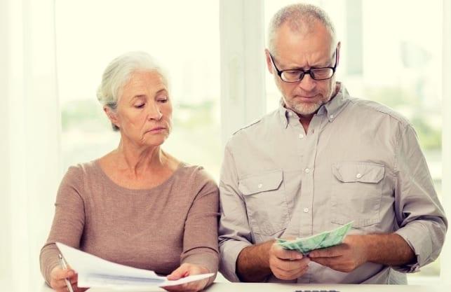 Älteres Paar prüft die Kosten einer Kreditaufnahme und vergleicht sie mit den Vorteilen des Immobilien-Teilverkaufs mit Nießbrauchrecht