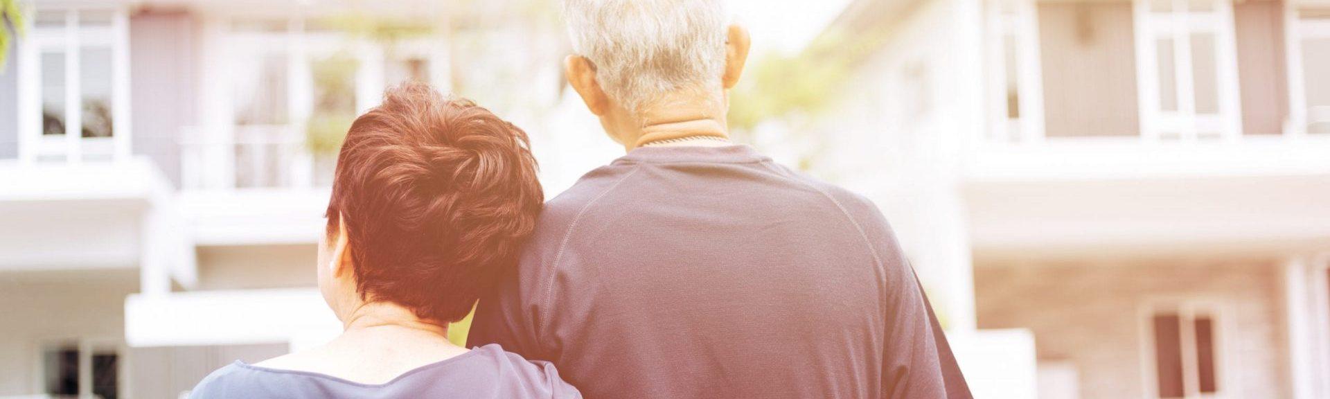 Zwei Senioren schauen auf ihr Haus, mit dem sie eine Immobilienrente erzielen können