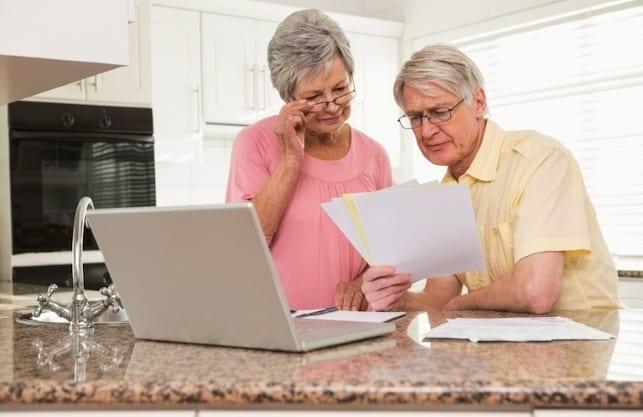 Zwei Senioren berechnen die zusätzliche finanzielle Flexibilität durch den Immobilien-Teilverkauf
