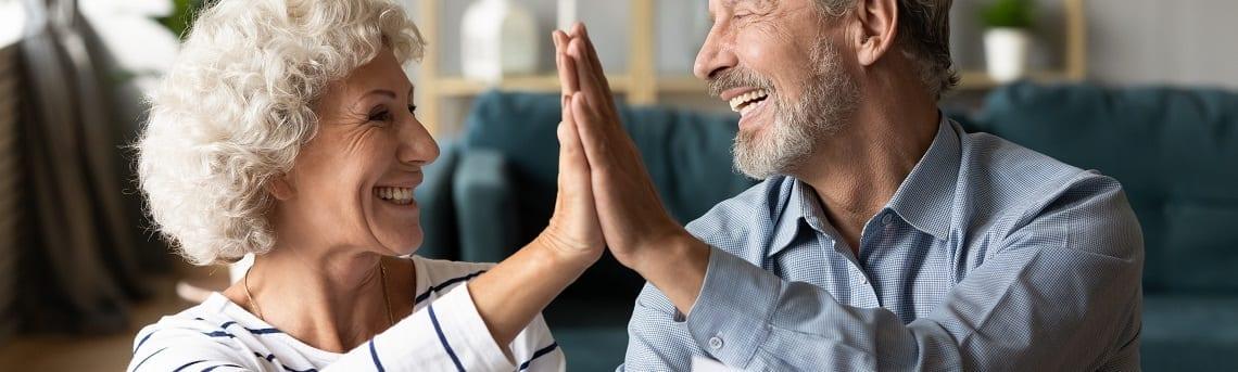 Altes Ehepaar schlägt ein und feiert den Grundbucheintrag ihres Nießbrauchrechts.