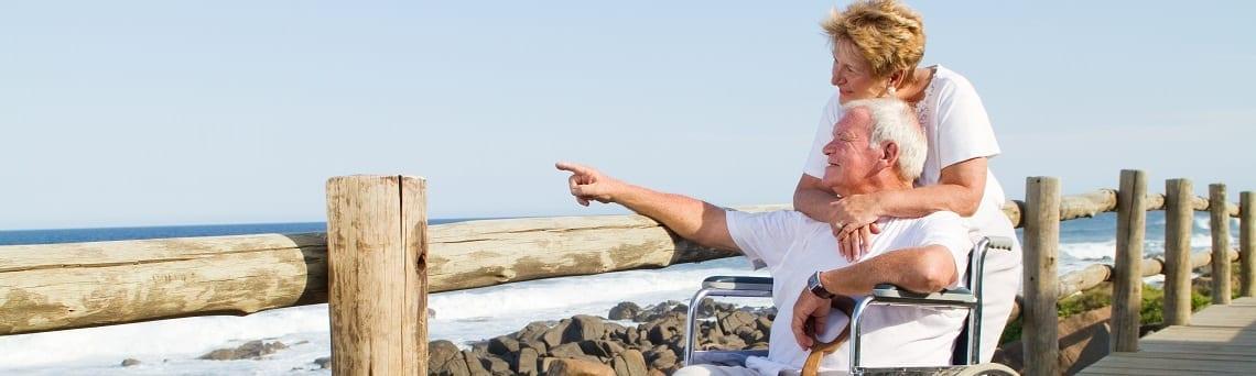 Pflegebedürftiger älterer Mann und seine Frau genießen einen Tag am Meer, dank Teilverkauf.