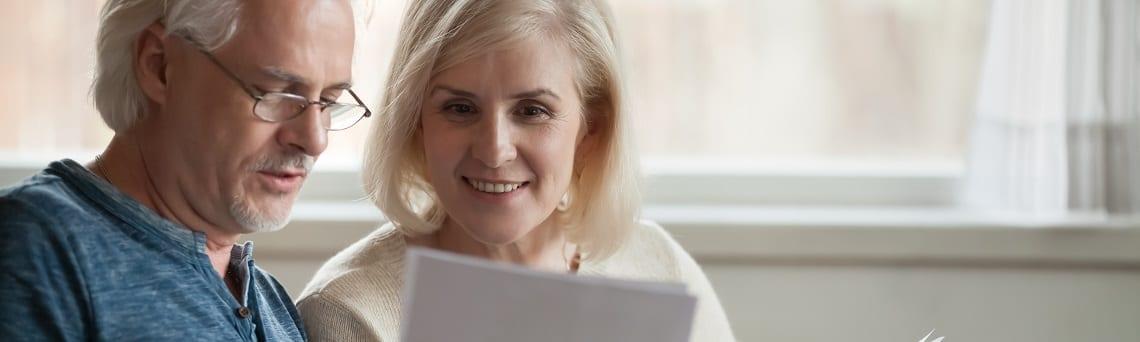 älteres Ehepaar berechnet das anfallende Nutzungsentgelt beim Teilverkauf.