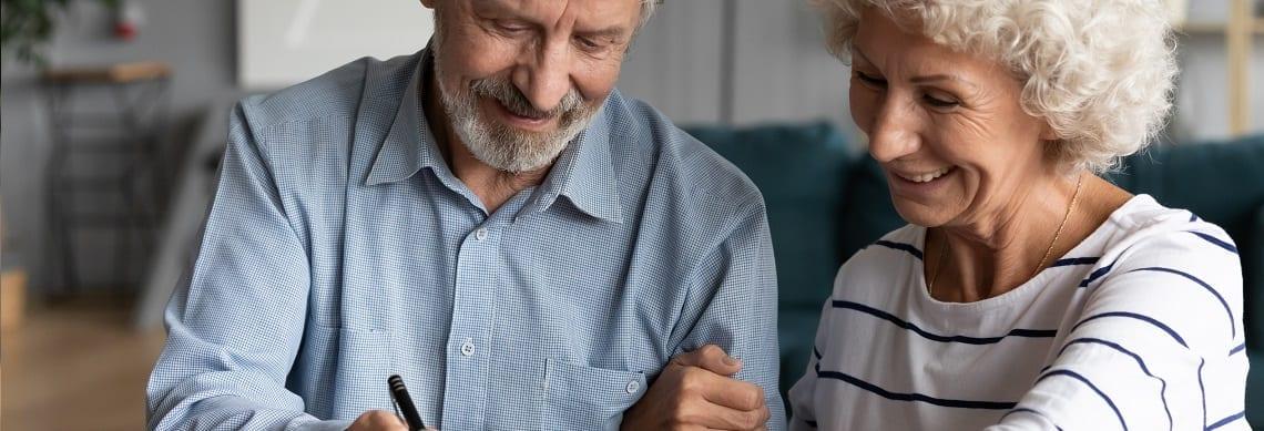 Altes Ehepaar unterschreibt den Teilverkaufsvertrag und lässt ihn notariell beurkunden.
