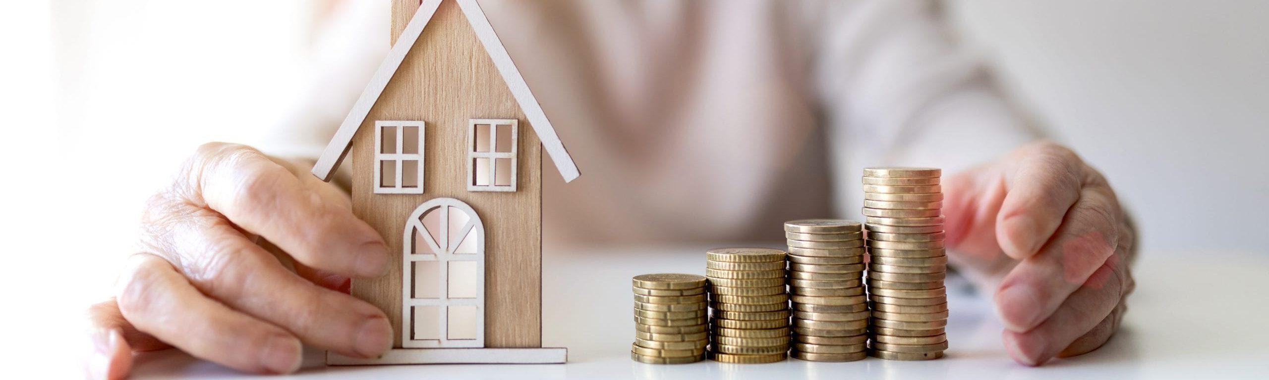 Ein Modellhaus neben Münzen in den Händen einer Seniorin