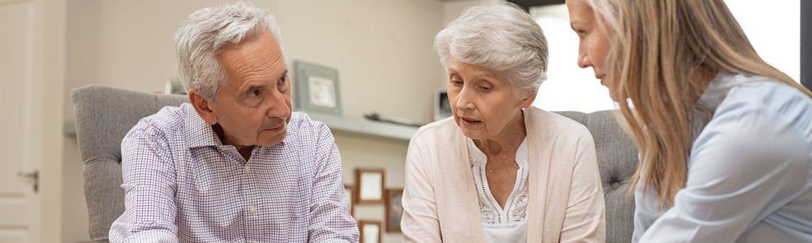 Das Foto zeigt eine Kauffrau die mit einem Rentnerpaar ihre zukünftigen Investitionsmöglichkeiten bespricht.