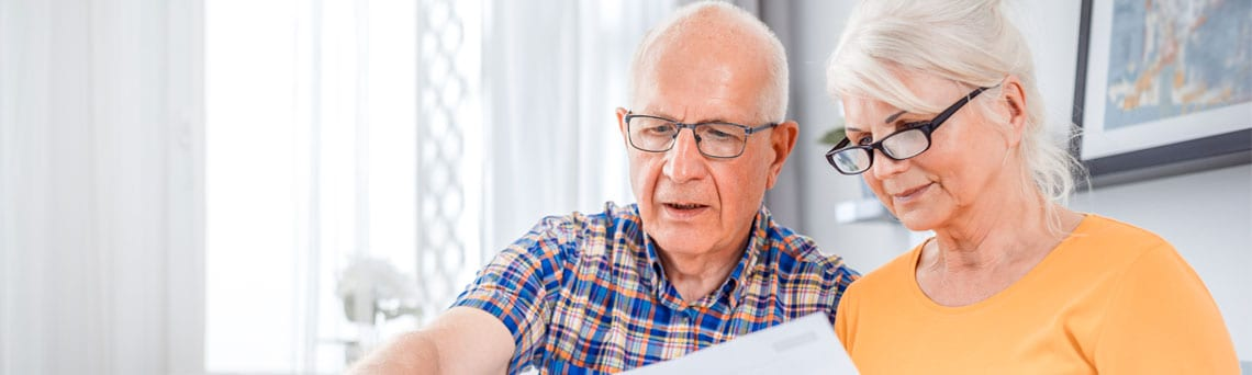 Das Foto zeigt ein älteres Paar welche gemeinsam Rechnungen an einem Laptop überprüfen.