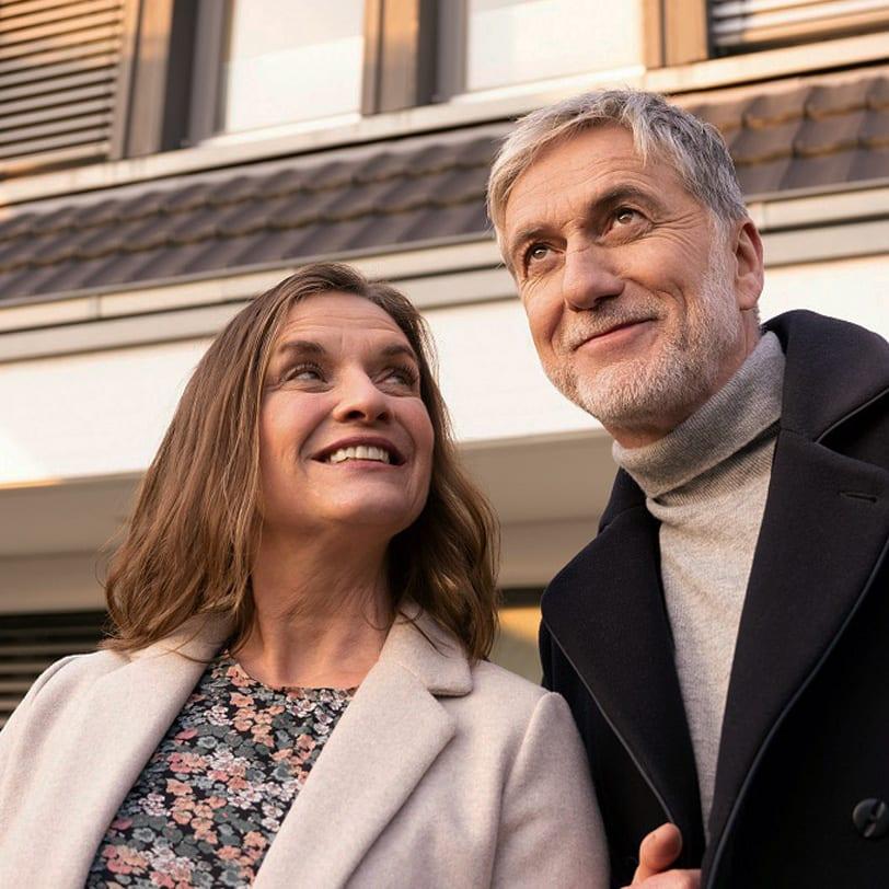 Das Foto zeigt ein älteres Paar das glücklich vor ihrem Haus steht.