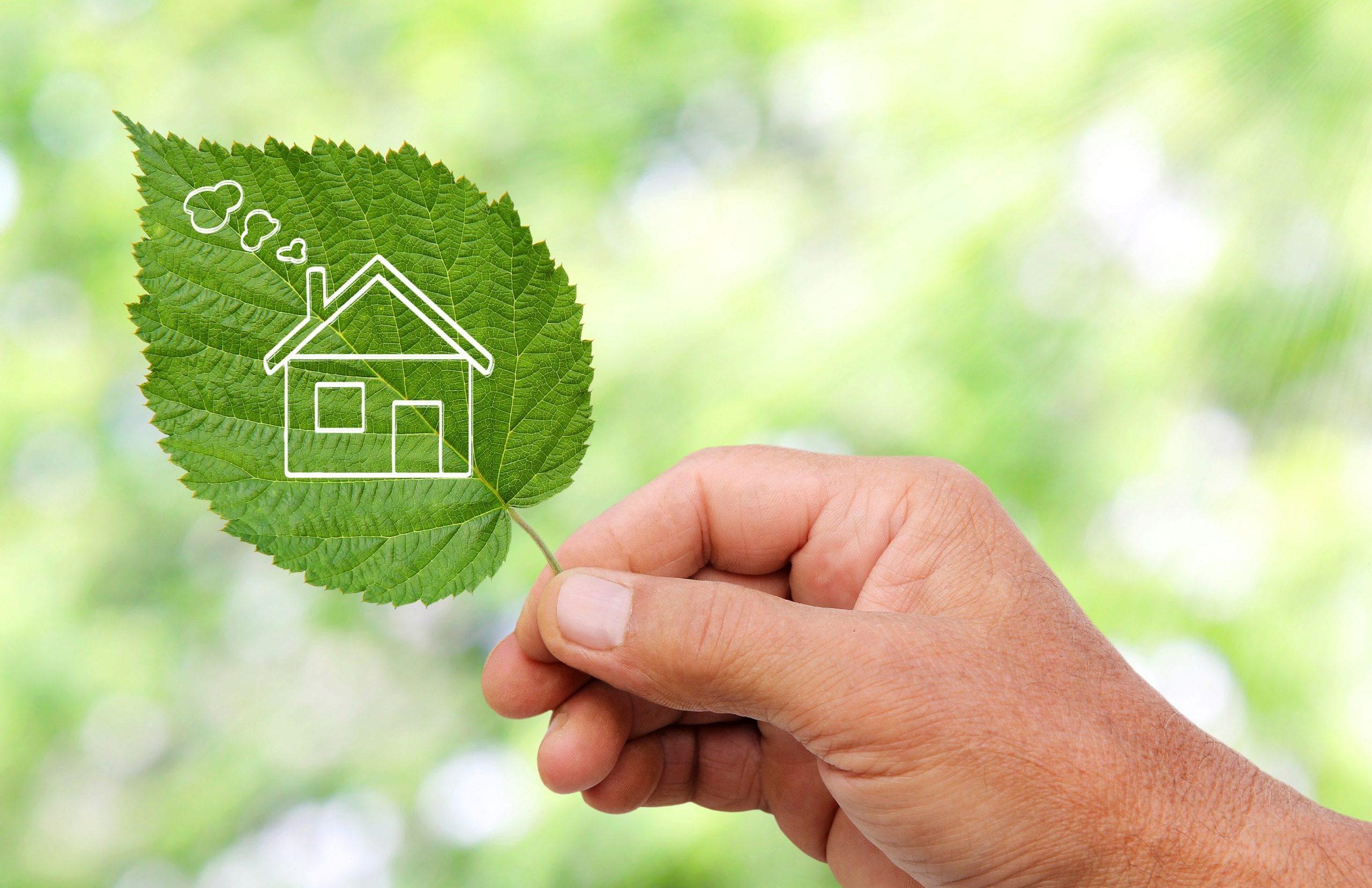 Eine Hand, die ein Blatt mit einem ausgeschnittenen Haus hält.