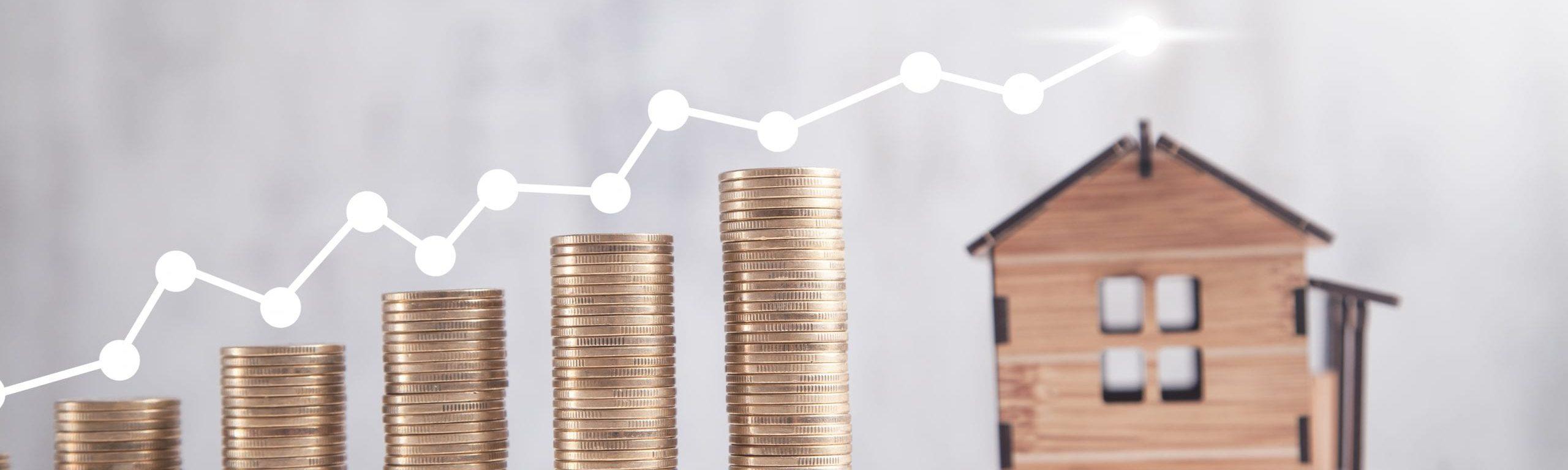 Gestapelte Münzen neben einem Hausmodell, die auf steigende Preise hindeuten