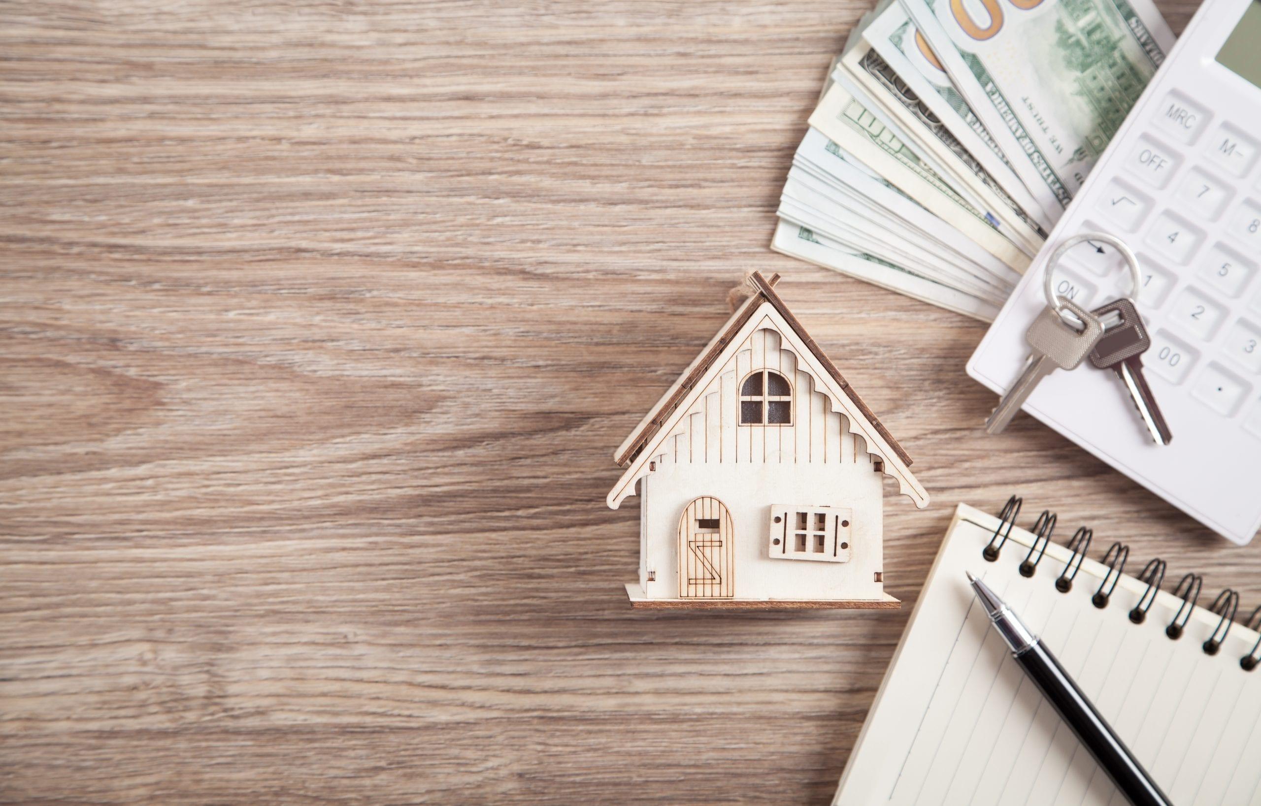 Hausmodell, Schlüssel, Geld und Taschenrechner liegend auf einem Tisch.