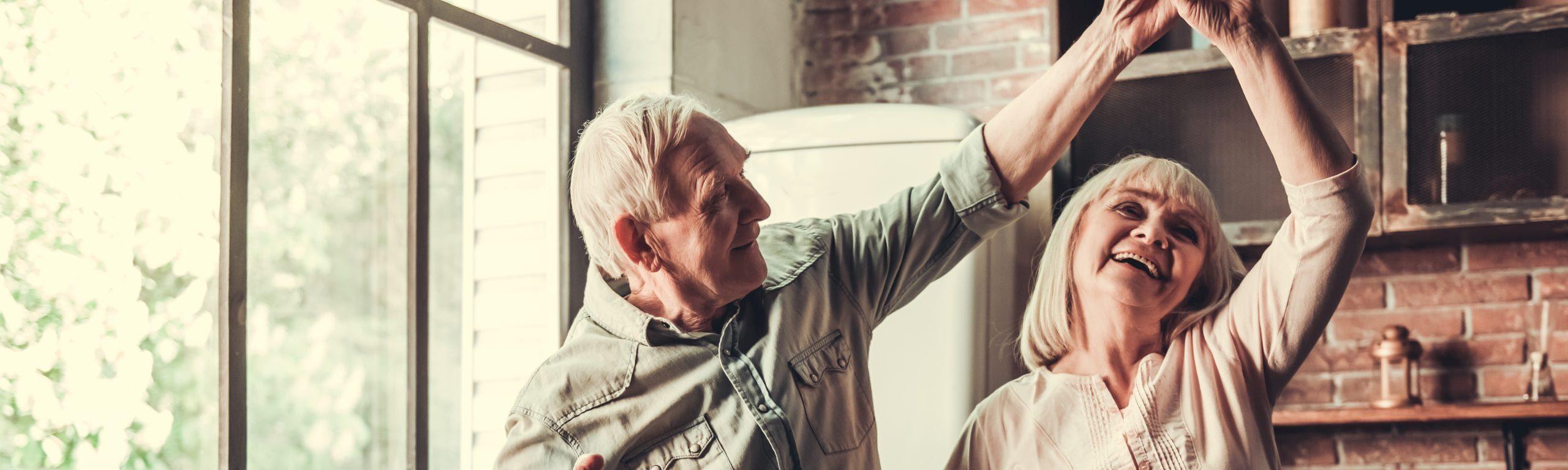 Seniorenpaar tanzt glücklich durch seine Küche.