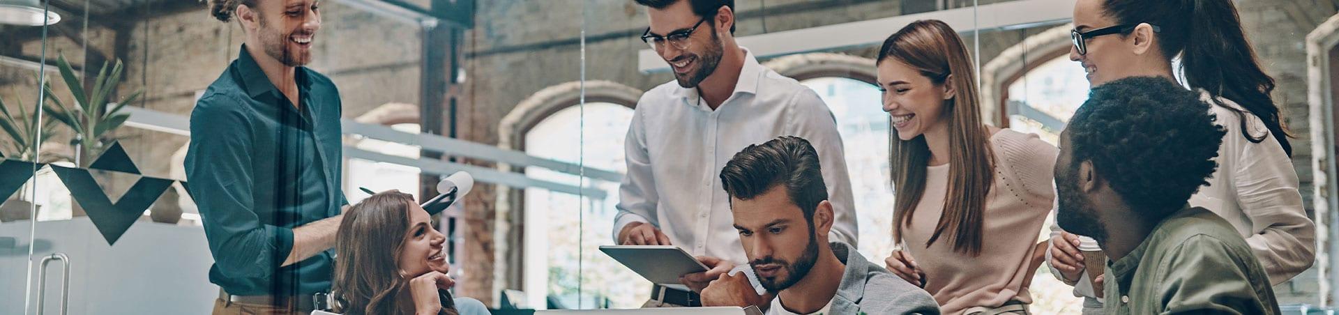 Das Foto zeigt ein junges fröhliches Team in einem Büro. Sie arbeiten gemeinsam an einem Projekt.
