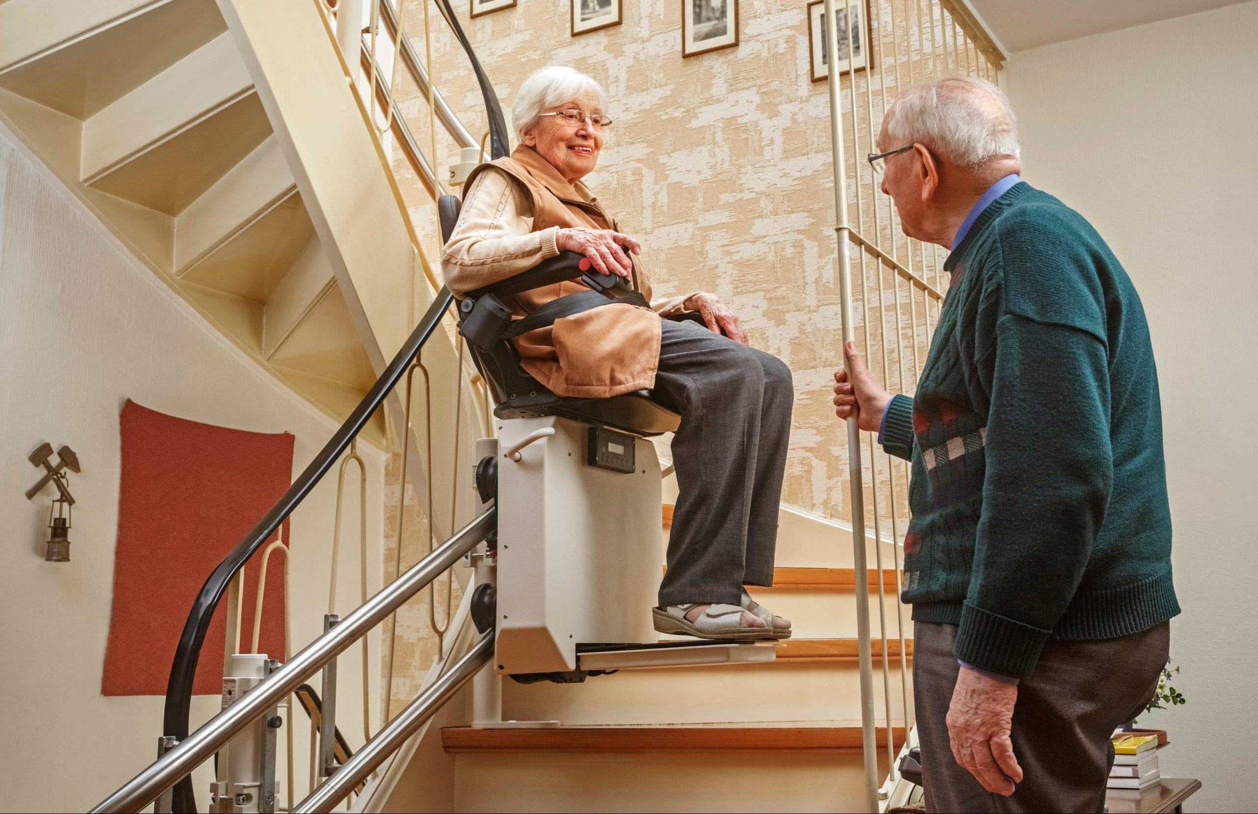 Älteres Ehepaar mit Treppenlift im Eigenheim.