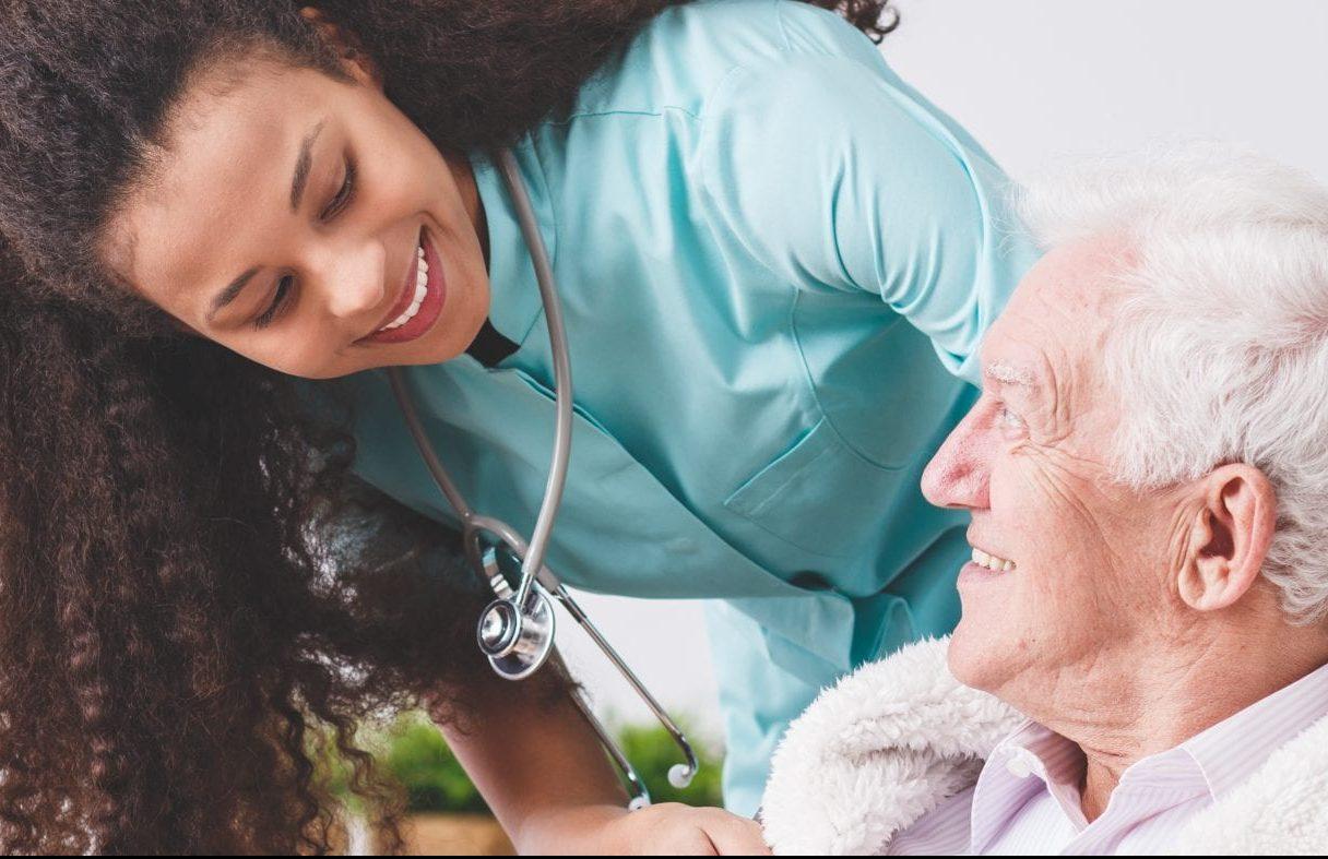 Weibliche Pflegekraft kümmert sich um älteren Herrn.