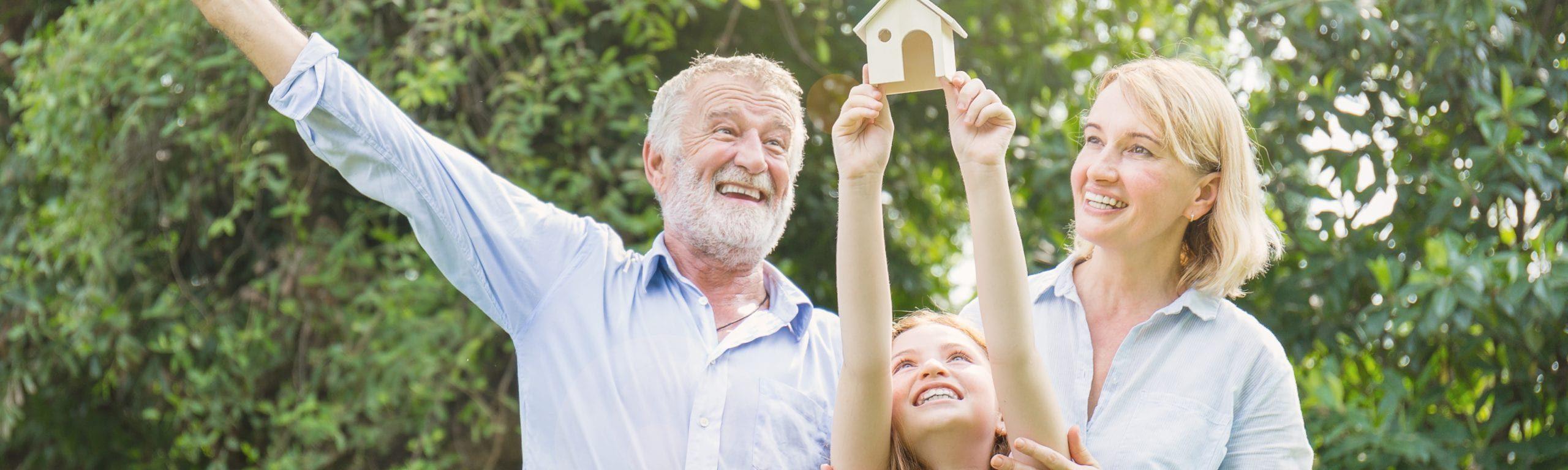 Glückliche Familie steht im Garten und hält ein Hausmodell in die Höhe.