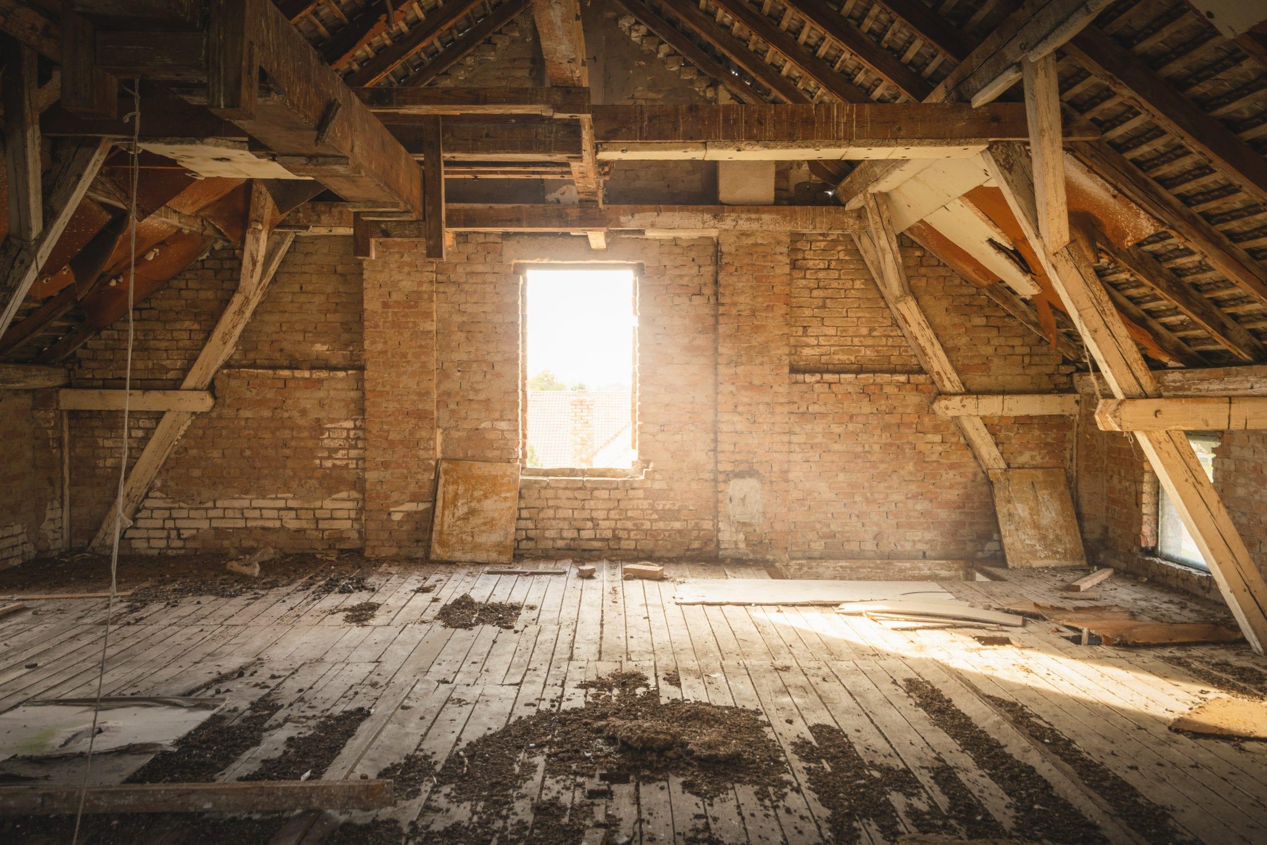 Renovierungsbedürftiger Dachboden mit Fenster, durch das Sonnenlicht hereinfällt