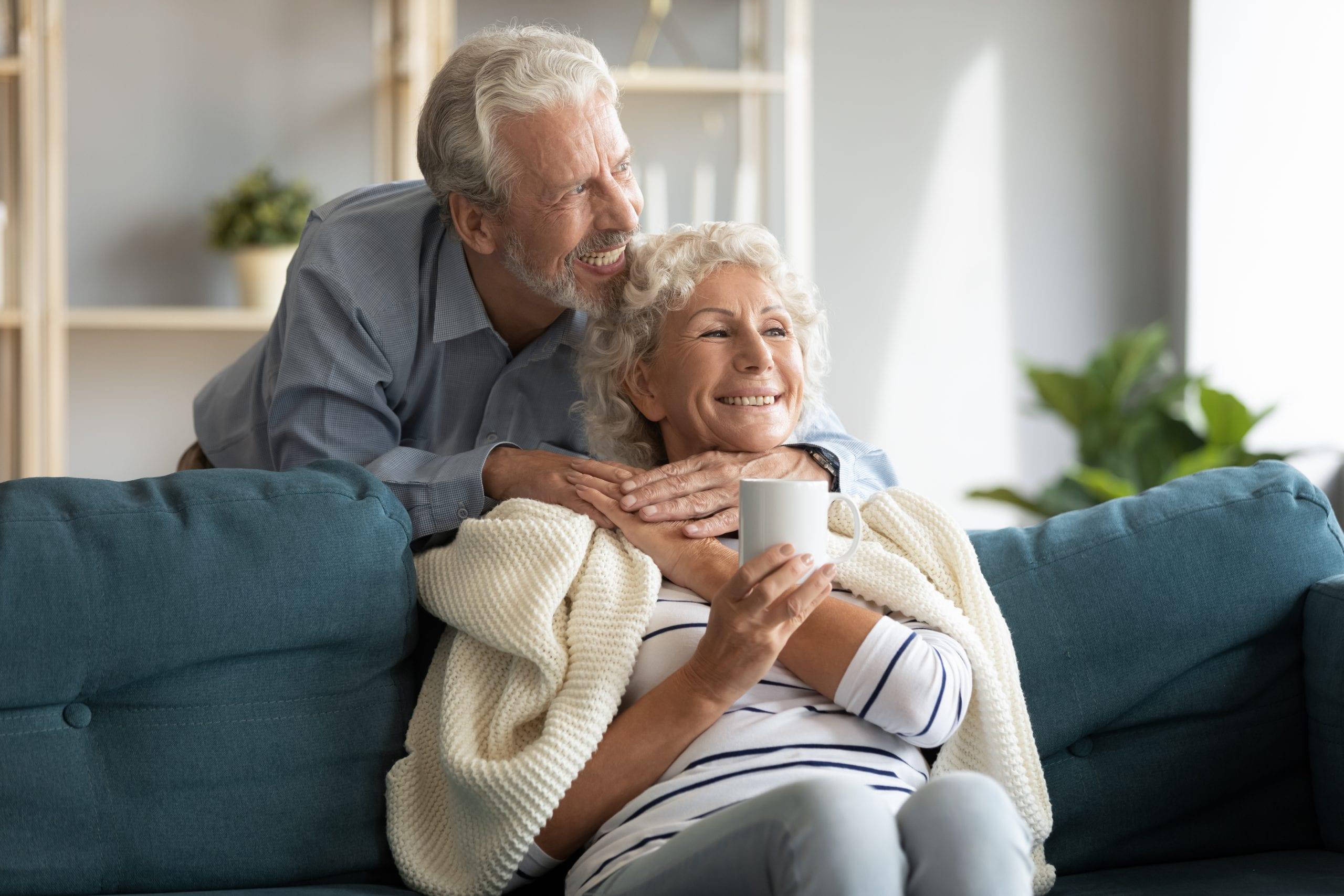 Zufriedener Rentner umarmt seine Ehefrau, die auf dem Sofa vor ihm sitzt