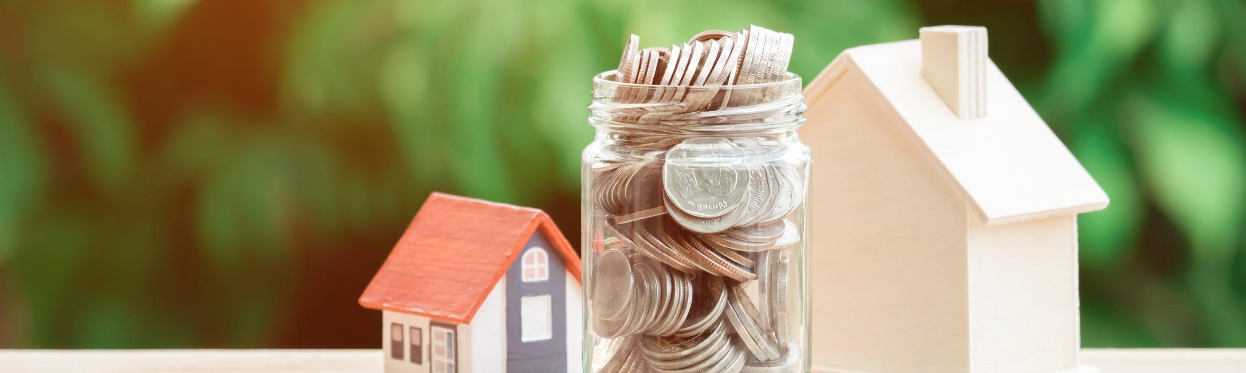 Ein Glas voller Münzen steht zwischen zwei Hausmodellen.