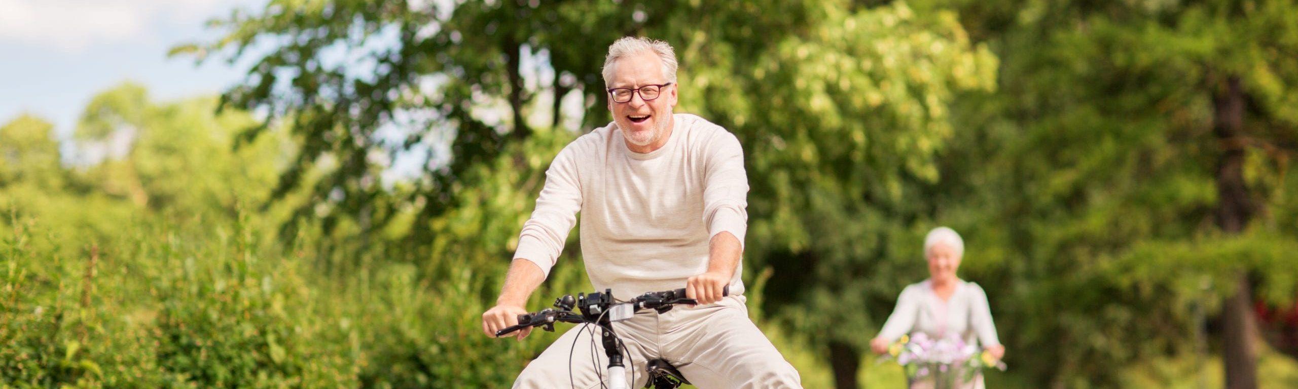Aktives Seniorenpärchen fährt Fahrrad, Mann lacht und lässt Beine baumeln