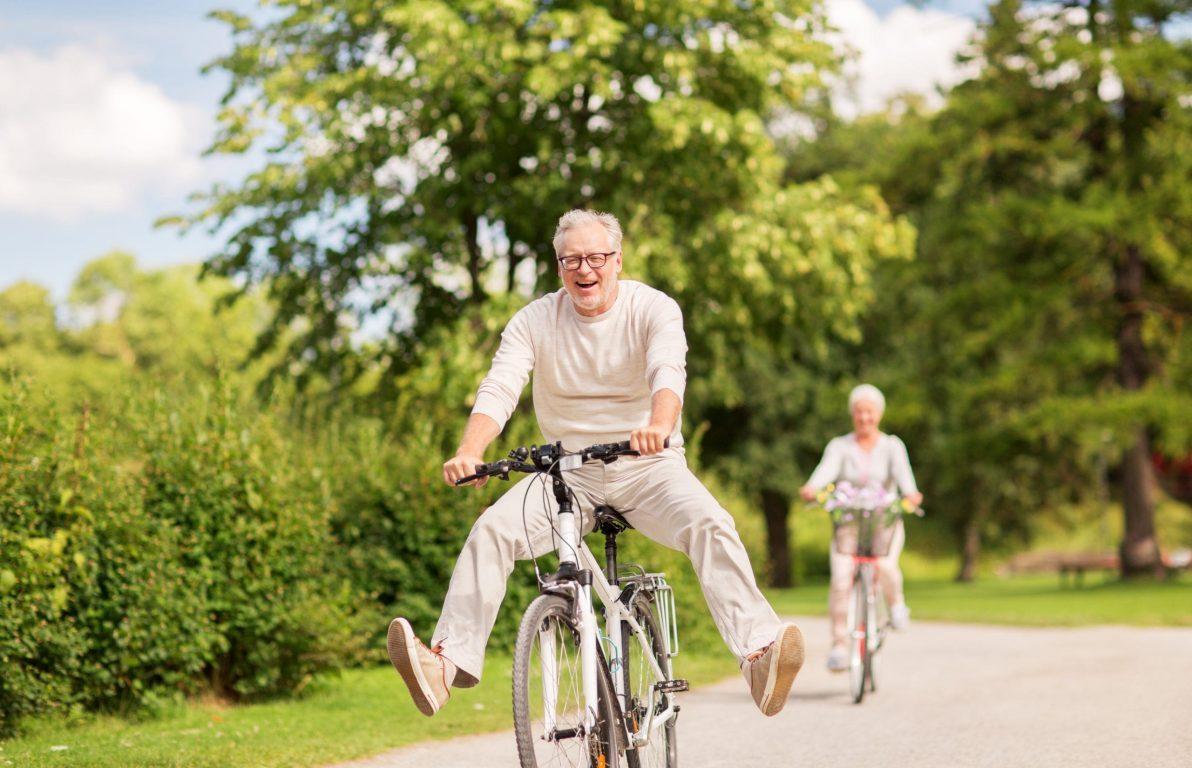 Aktives Seniorenpärchen fährt Fahrrad, Mann lacht und lässt die Beine baumeln