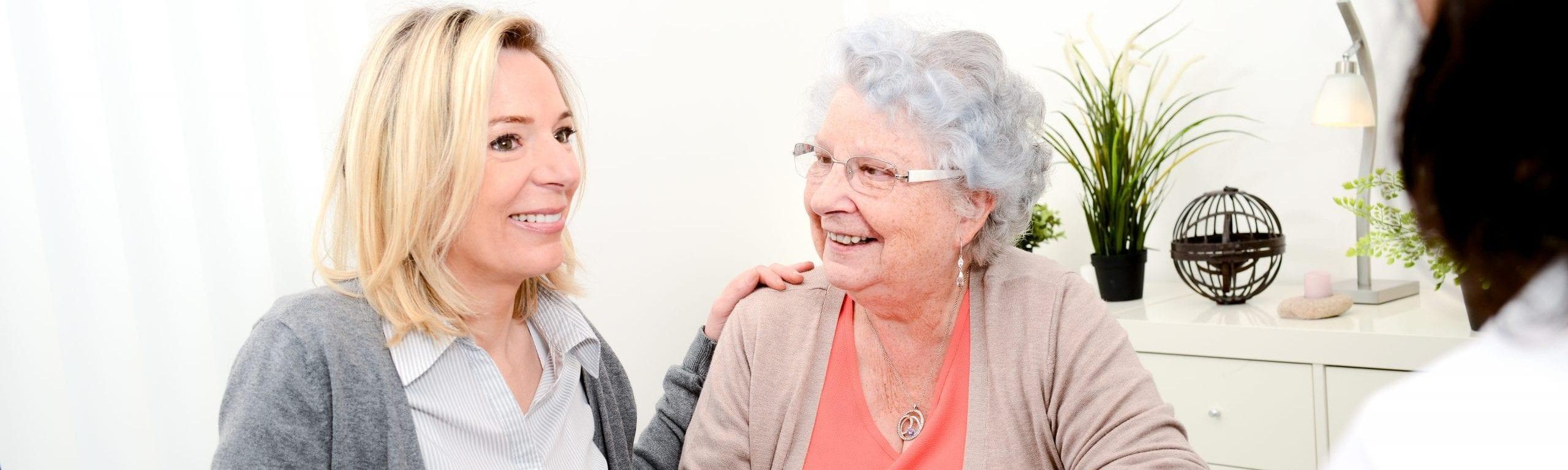 Das Foto zeigt eine jüngere und eine ältere Frau die sich anlächeln.