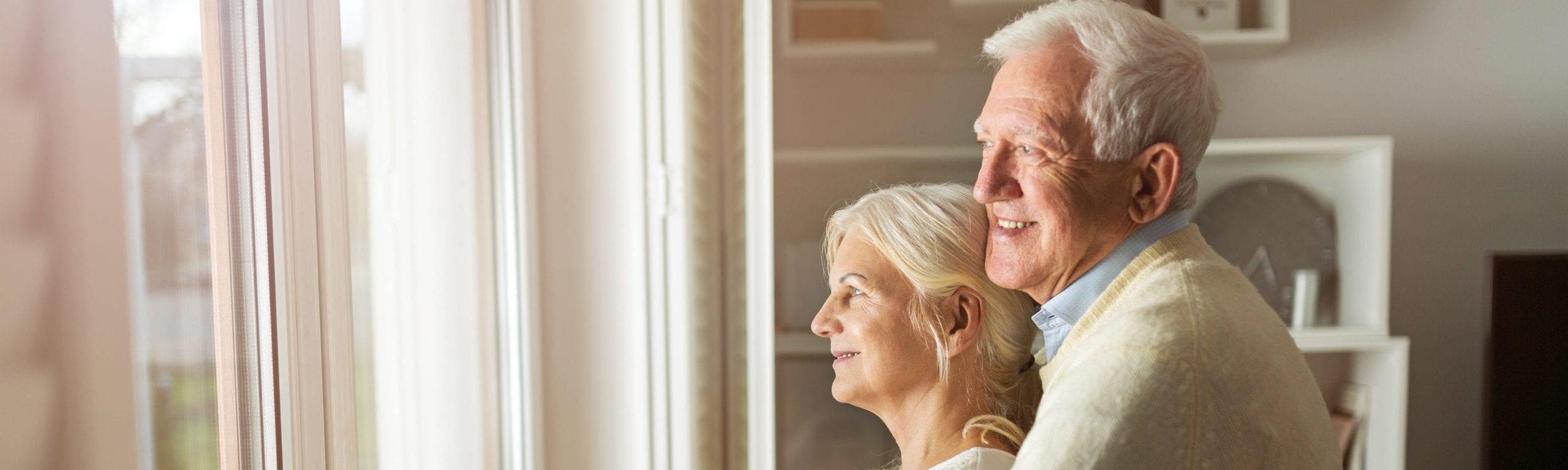 Zufriedener Rentner umarmt seine Ehefrau.