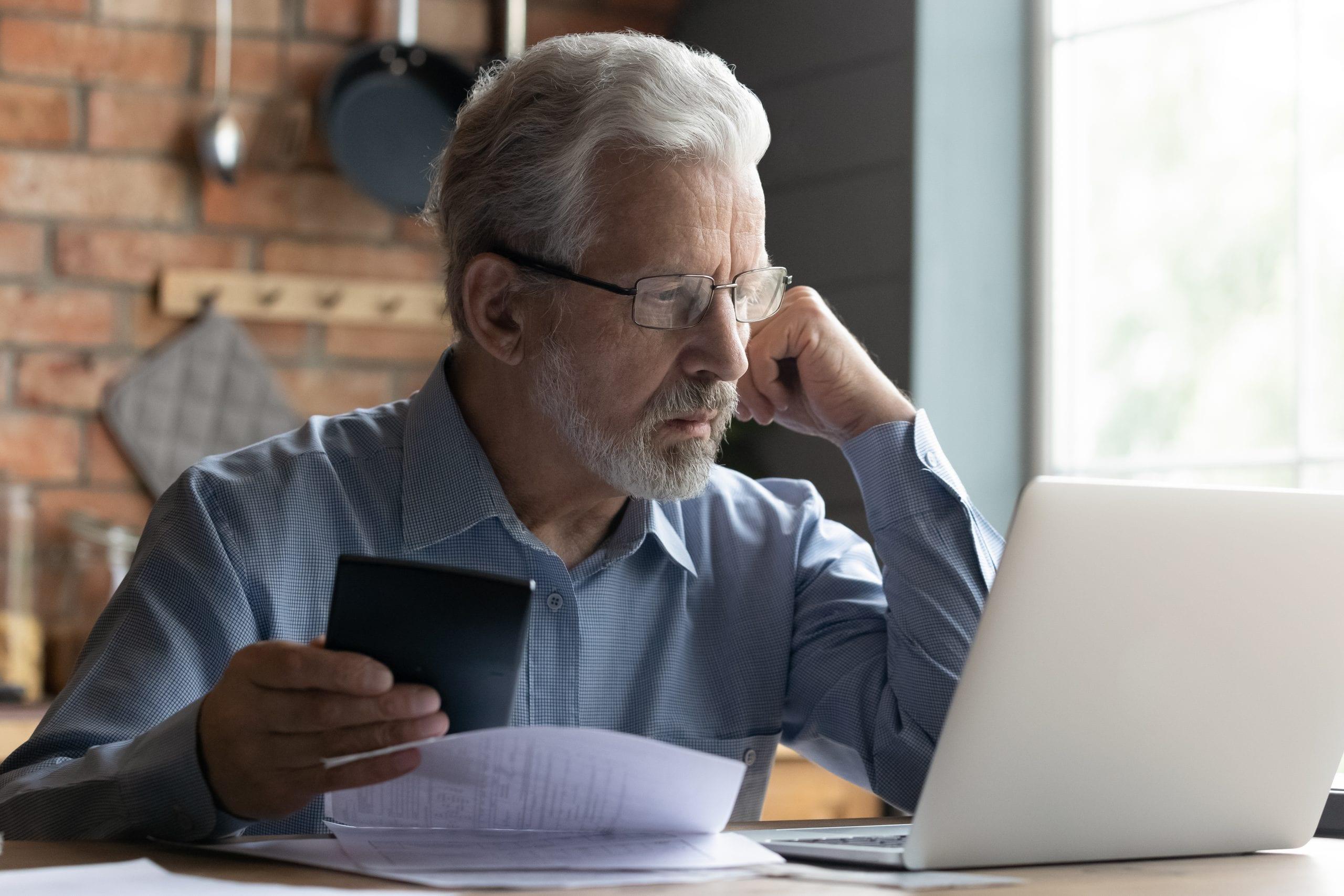 Ein älterer Mann sitzt mit Taschenrechner und Laptop an seinen Steuern. Er sieht Hilflos aus.