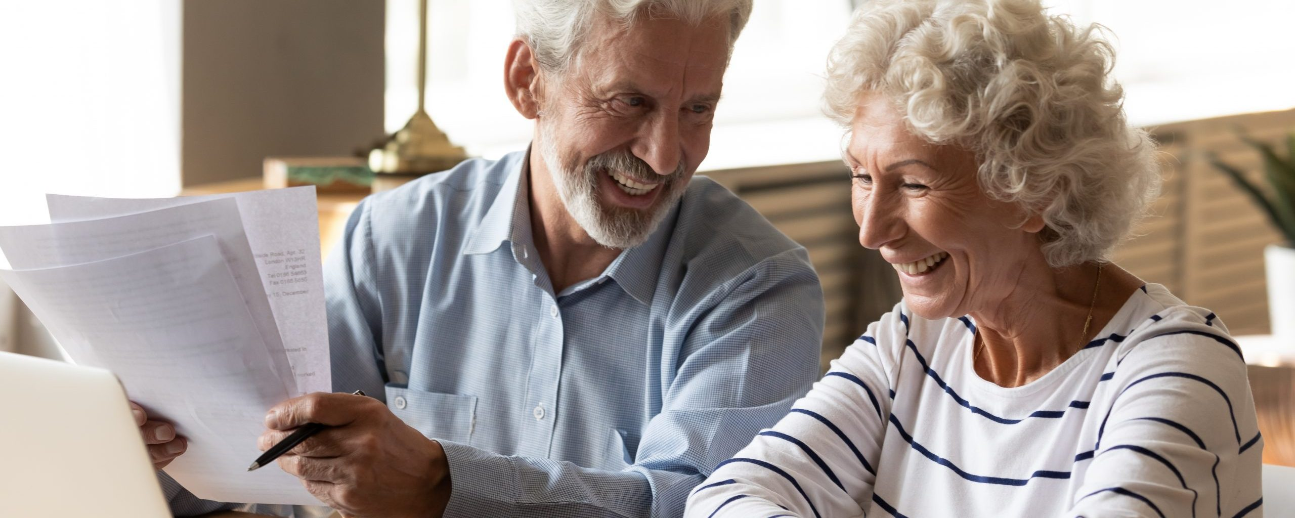 Lächelndes Seniorenpaar vor einem Laptop.