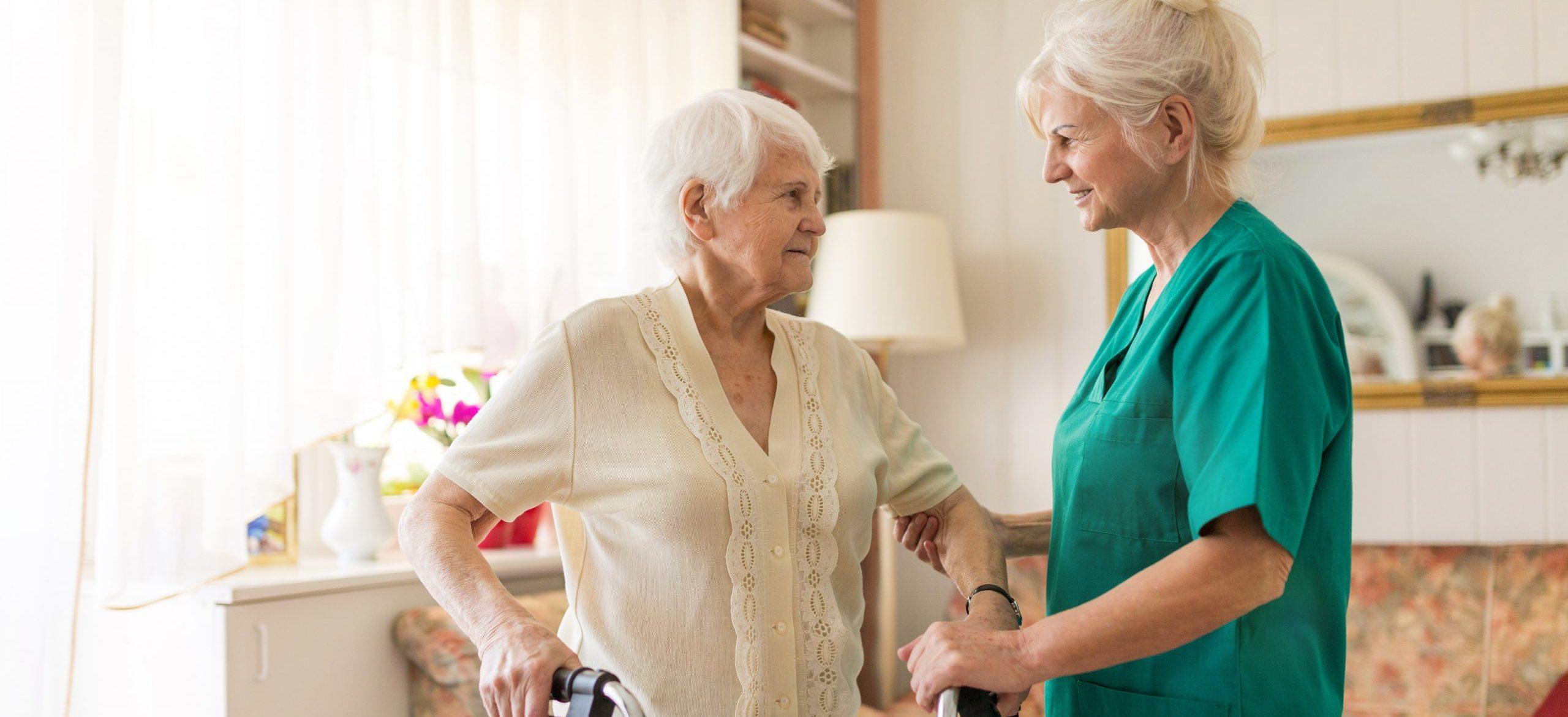 Pflegekraft unterstützt eine Seniorin.