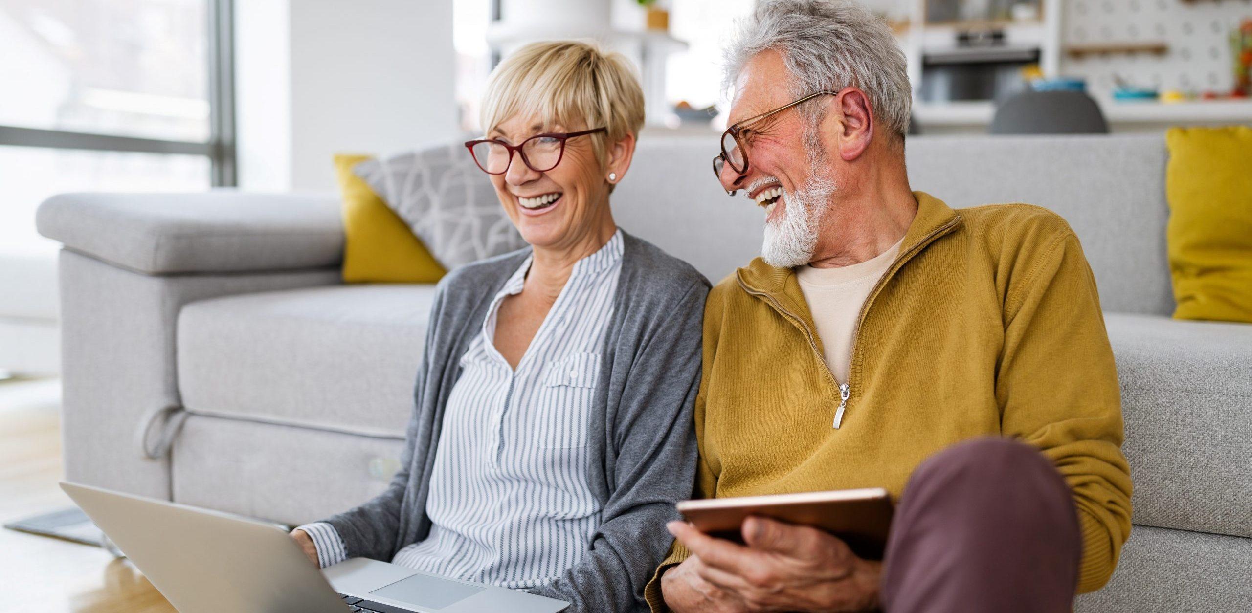 Glückliches Seniorenpaar informiert sich über Hypothekendarlehen.